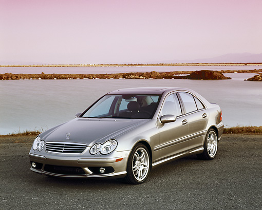 AUT 05 RK0373 03 © Kimball Stock 2005 Mercedes C55 AMG Sports Sedan Silver 3/4 Front View By Water