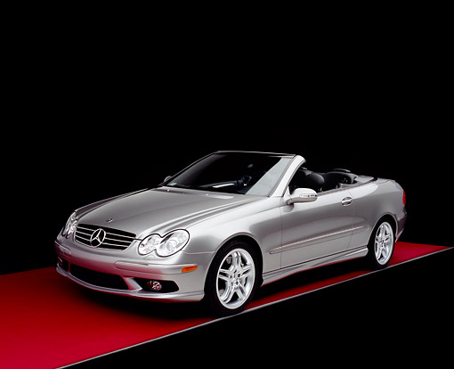 AUT 05 RK0386 01 © Kimball Stock 2005 Mercedes-Benz CLK55 Convertible Silver 3/4 Front View On Red Floor Studio