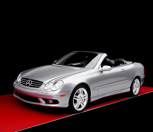 AUT 05 RK0386 02 © Kimball Stock 2005 Mercedes-Benz CLK55 Convertible Silver 3/4 Front View On Red Floor Studio