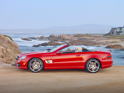 AUT 05 RK0624 01 © Kimball Stock 2010 Mercedes-Benz SL63 Convertible Red Profile View On Beach By Houses