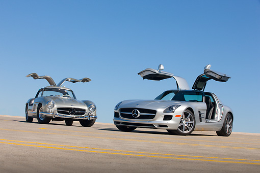 AUT 05 RK0659 01 © Kimball Stock 1956 Mercedes-Benz 300 SL Gullwing Coupe And 2011 Mercedes-Benz SLS AMG Silver 3/4 Front View On Roof Of Parking Garage