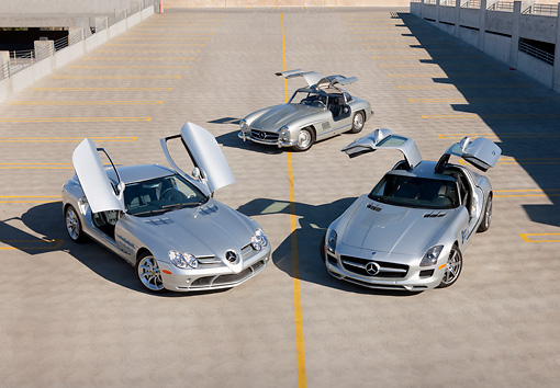 AUT 05 RK0660 01 © Kimball Stock 2009 Mercedes-Benz McLaren SLR Stirling Moss, 1956 Mercedes-Benz 300 SL Gullwing Coupe And 2011 Mercedes-Benz SLS AMG Silver 3/4 Front View On Roof Of Parking Garage