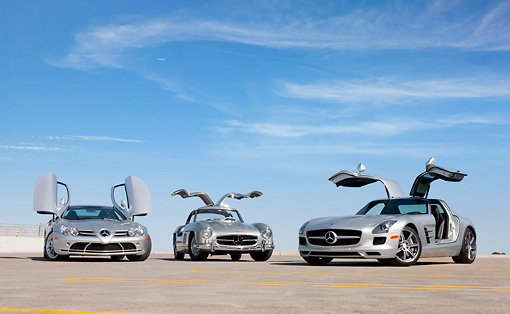 AUT 05 RK0661 01 © Kimball Stock 2009 Mercedes-Benz McLaren SLR Stirling Moss Roadster, 1956 Mercedes-Benz 300 SL Gullwing Coupe And 2011 Mercedes-Benz SLS AMG Silver 3/4 Front View On Roof Of Parking Garage