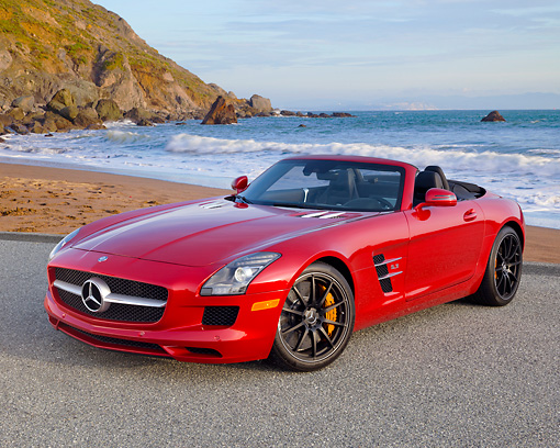AUT 05 RK0675 01 © Kimball Stock 2012 Mercedes-Benz SLS Roadster Red 3/4 Front View On Pavement By Beach