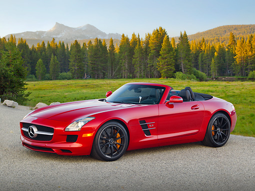 AUT 05 RK0679 01 © Kimball Stock 2012 Mercedes-Benz SLS Roadster Red 3/4 Side View On Pavement By Meadow And Trees