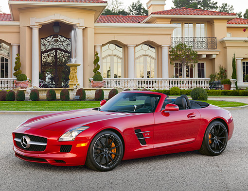 AUT 05 RK0693 01 © Kimball Stock 2012 Mercedes-Benz SLS Roadster Red 3/4 Side View On Pavement By Mansion