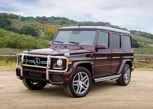 AUT 05 RK0697 01 © Kimball Stock 2013 Mercedes-Benz G63 AMG Maroon 3/4 Front View On Dirt By Hills
