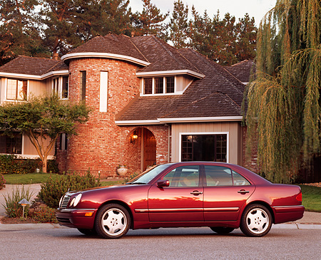 AUT 05 RK0013 02 © Kimball Stock 1999 Mercedes-Benz E420 Sedan Sport Burgundy 3/4 Front View On Pavement By House