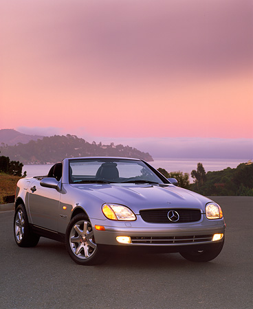 AUT 05 RK0033 02 © Kimball Stock 1998 Mercedes-Benz SLK Kompressor Convertible Silver 3/4 Front View On Pavement Pink Sky