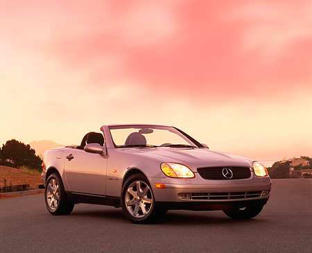 AUT 05 RK0036 03 © Kimball Stock 1998 Mercedes SLK Kompressor Convertible Silver 3/4 Front On Road Lights On By Trees At Dusk