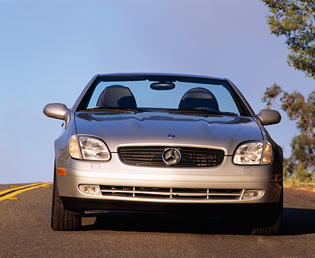 AUT 05 RK0046 03 © Kimball Stock 1998 Mercedes-Benz SLK Kompressor Convertible Silver Head On Shot On Pavement Blue Sky