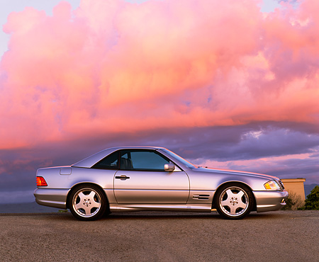 AUT 05 RK0072 04 © Kimball Stock 1997 Silver 500SL Mercedes Sport Profile On Pavement At Dusk Blue Sky Purple Clouds