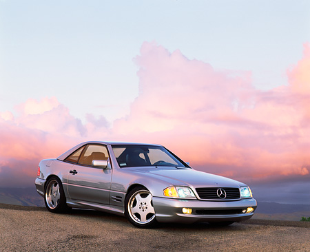 AUT 05 RK0074 04 © Kimball Stock 1997 Silver 500SL Mercedes Sport 3/4 Front View On Pavement Headlights On At Dusk Purple Clouds