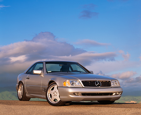 AUT 05 RK0075 06 © Kimball Stock 1997 Mercedes-Benz 500SL Sport Silver 3/4 Front View Blue Sky Gray Clouds