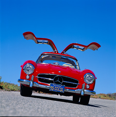 AUT 05 RK0098 08 © Kimball Stock 1955 Mercedes-Benz Gullwing Red Low Slanted Head On Pavement Blue Sky