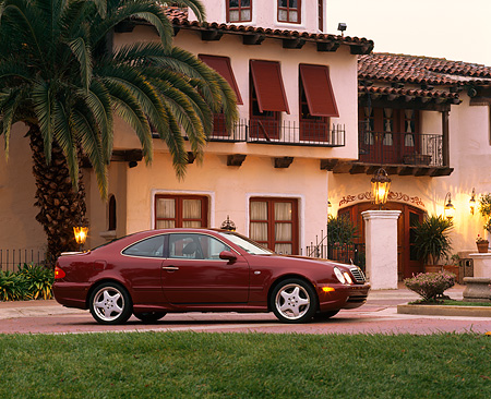 AUT 05 RK0135 02 © Kimball Stock 1999 Mercedes Benz CLK 430 Sport Coupe Bordeaux Red 3/4 Front View By Spanish Building