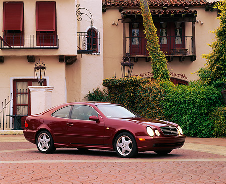 AUT 05 RK0140 05 © Kimball Stock 1999 Mercedes-Benz CLK 430 Sport Coupe Bordeaux Red Side 3/4 View By Spanish Building