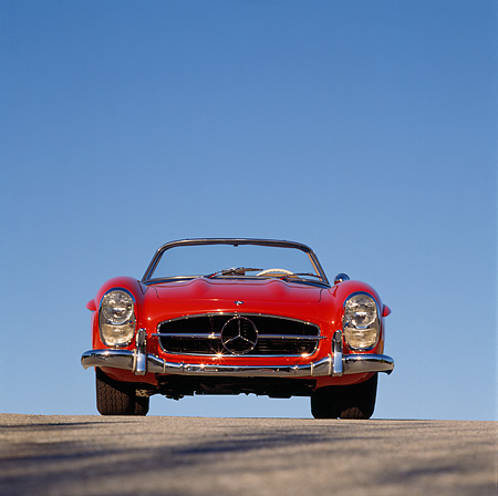 AUT 05 RK0145 01 © Kimball Stock Mercedes-Benz 300SL Convertible Red Low Head On Shot On Pavement Blue Sky