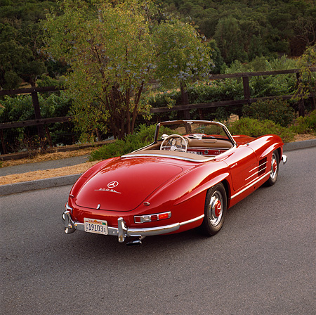 AUT 05 RK0149 03 © Kimball Stock 1957 Mercedes-Benz 300SL Convertible Red 3/4 Rear View On Pavement Hill By Bushes
