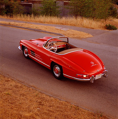 AUT 05 RK0150 02 © Kimball Stock Mercedes-Benz 300SL Convertible Red Overhead 3/4 Rear View On Pavement