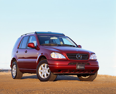 AUT 05 RK0172 02 © Kimball Stock 2000 Mercedes-Benz ML430 Burgundy Low 3/4 Front View On Dirt Blue Sky