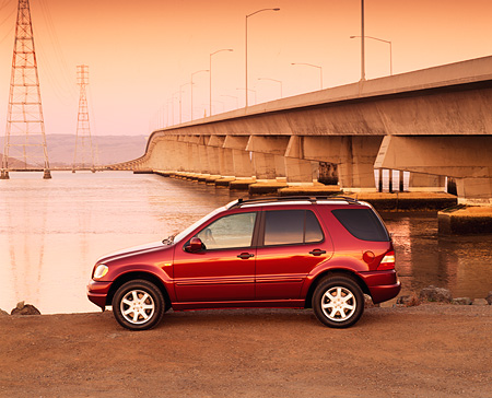 AUT 05 RK0175 01 © Kimball Stock 2000 Mercedes-Benz ML430 Burgundy Profile By Bridge And Water