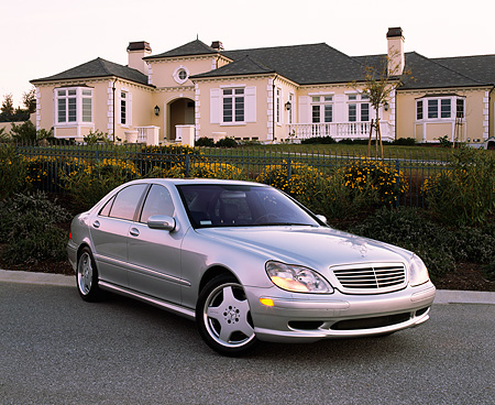 AUT 05 RK0261 05 © Kimball Stock 2002 Mercedes-Benz S500 Class Silver 3/4 Front View On Pavement By House