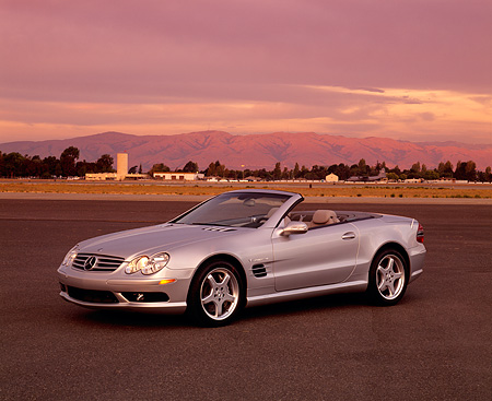 AUT 05 RK0292 01 © Kimball Stock 2003 Mercedes SL55 AMG Roadster Silver 3/4 Front View On Pavement Mountains Background Filtered
