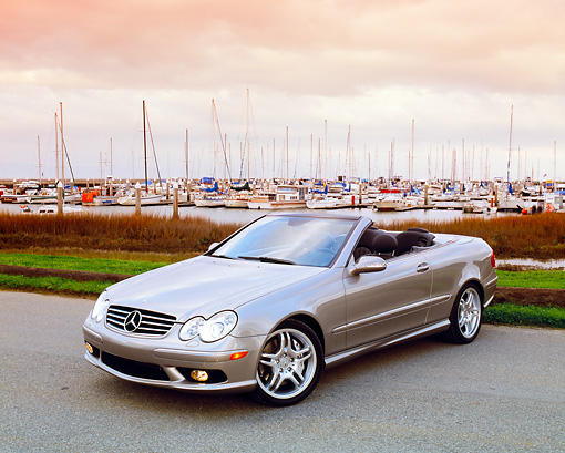 AUT 05 RK0377 02 © Kimball Stock 2005 Mercedes CLK55 Silver Convertible 3/4 Front View On Pavement By Harbor Filtered