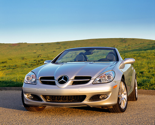 AUT 05 RK0396 01 © Kimball Stock 2005 Mercedes-Benz SLK350 Convertible Silver 3/4 Front View On Pavement By Grass Hills