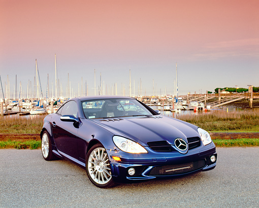 AUT 05 RK0423 01 © Kimball Stock 2005 Mercedes SLK55 Roadster Blue 3/4 Front View On Pavement By Harbor Filtered
