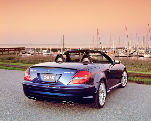 AUT 05 RK0425 02 © Kimball Stock 2005 Mercedes-Benz SLK55 Roadster Blue 3/4 Rear View On Pavement By Harbor Filtered