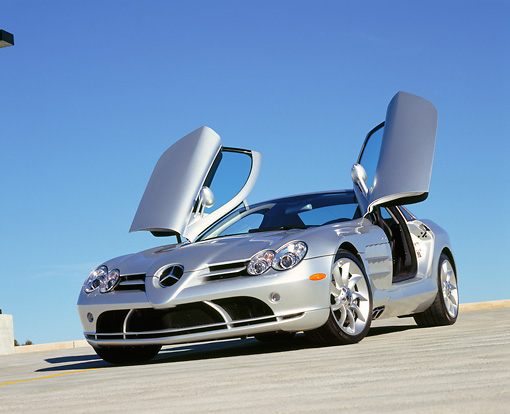 AUT 05 RK0429 03 © Kimball Stock 2005 Mercedes-Benz SLR McLaren Silver Low 3/4 Front View Butterfly Doors On Pavement Blue Sky