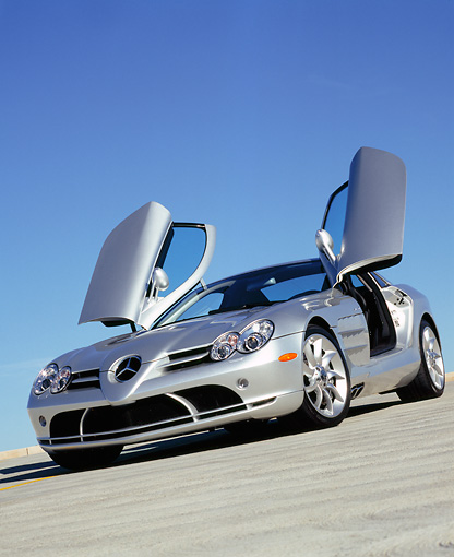 AUT 05 RK0429 11 © Kimball Stock 2005 Mercedes-Benz SLR McLaren Silver Low 3/4 Front View Butterfly Doors On Pavement Blue Sky