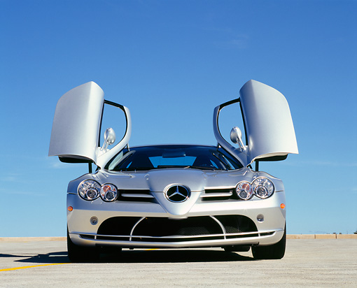 AUT 05 RK0431 01 © Kimball Stock 2005 Mercedes-Benz SLR McLaren Silver Low Head On View Butterfly Doors On Pavement Blue Sky