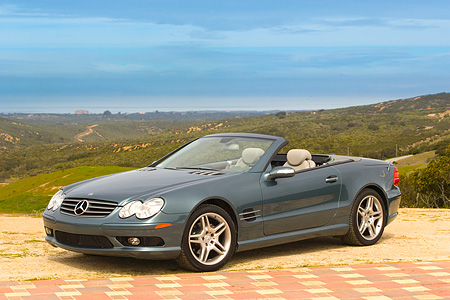 AUT 05 RK0486 01 © Kimball Stock 2006 Mercedes-Benz SL500 Convertible Blue 3/4 Front View Mountains Background