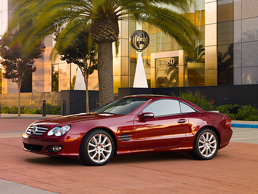 AUT 05 RK0505 01 © Kimball Stock 2007 Mercedes-Benz SL550 Roadster Storm Red 3/4 Side View On Pavement By Building