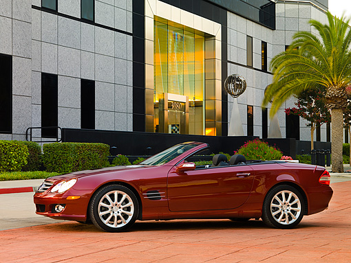 AUT 05 RK0507 01 © Kimball Stock 2007 Mercedes-Benz SL550 Roadster Storm Red 3/4 Front View On Pavement By Building