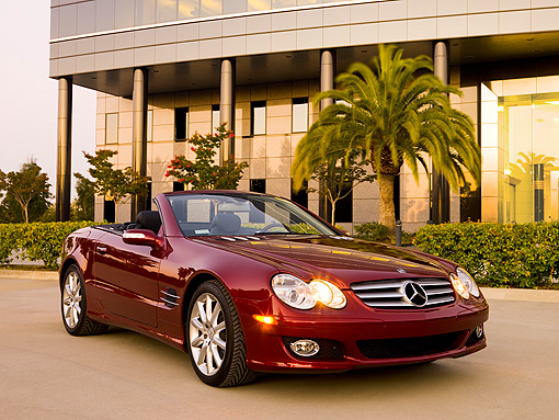 AUT 05 RK0508 01 © Kimball Stock 2007 Mercedes-Benz SL550 Roadster Storm Red 3/4 Front View On Pavement By Building