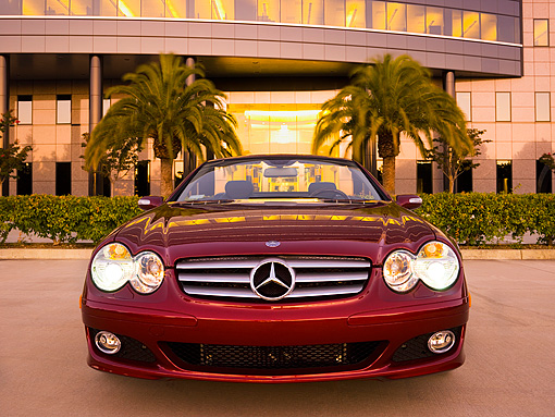AUT 05 RK0509 01 © Kimball Stock 2007 Mercedes-Benz SL550 Roadster Storm Red Low Head On View On Pavement By Building