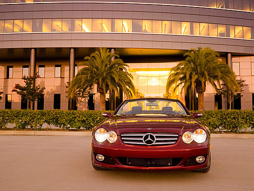 AUT 05 RK0510 01 © Kimball Stock 2007 Mercedes-Benz SL550 Roadster Storm Red Low Head On View On Pavement By Building