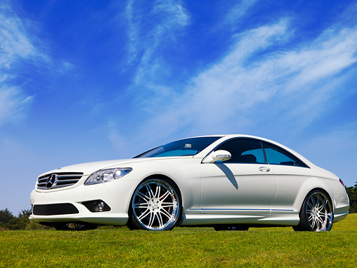 AUT 05 RK0567 01 © Kimball Stock 2007 Mercedes-Benz CL550 White Front 3/4 View Low Angle On Grass Blue Sky