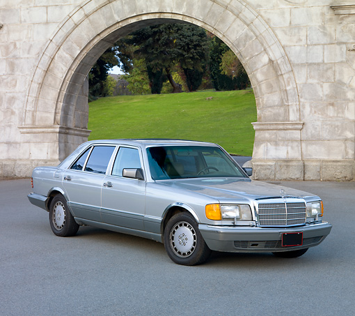 AUT 05 RK0574 01 © Kimball Stock 1986 Mercedes-Benz 420 SEL Silver 3/4 Front View On Pavement By Stone Arch