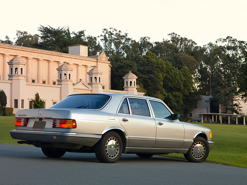 AUT 05 RK0581 01 © Kimball Stock 1986 Mercedes-Benz 420 SEL Silver 3/4 Rear View On Pavement By Building