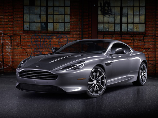 AUT 06 BK0007 01 © Kimball Stock 2012 Aston Martin DB9 Gray 3/4 Front View By Brick Building With Graffiti