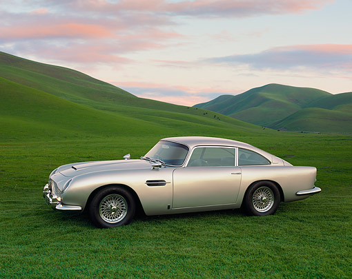 AUT 06 RK0012 04 © Kimball Stock 1964 Aston Martin DB5 Silver Side 3/4 View On Grass By Hills Filtered