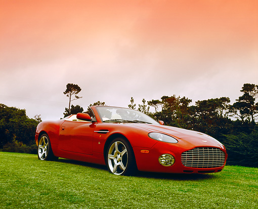 AUT 06 RK0022 02 © Kimball Stock 2005 Aston Martin Zagato Roadster Burgundy 3/4 Front View On Grass By Hill