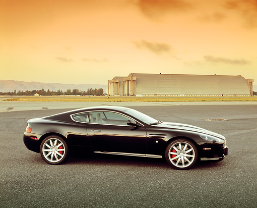 AUT 06 RK0060 02 © Kimball Stock 2005 Aston Martin DB9 Coupe Black Profile On Pavement By Airplane Hanger Filtered