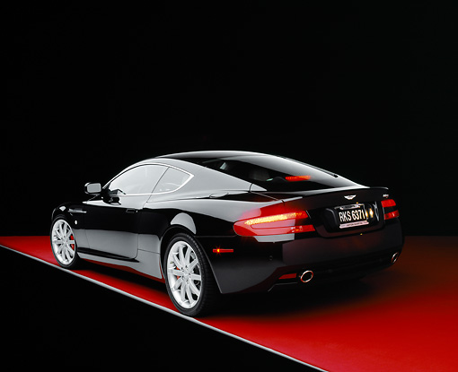 AUT 06 RK0063 01 © Kimball Stock 2005 Aston Martin DB9 Coupe Black 3/4 Rear View On Red Floor Studio