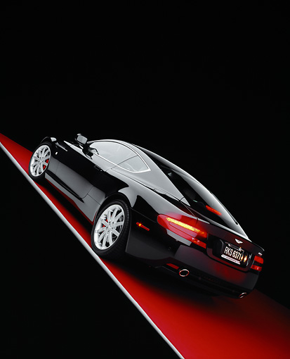 AUT 06 RK0064 06 © Kimball Stock 2005 Aston Martin DB9 Coupe Black Slanted 3/4 Rear View On Red Floor Studio